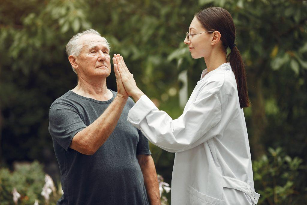 Terapeuta ocupacional chocando la mano con anciano